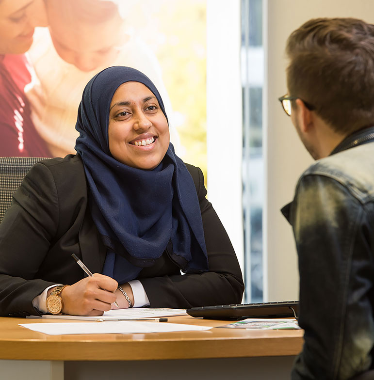 A staff member in a hijab speaking to a customer